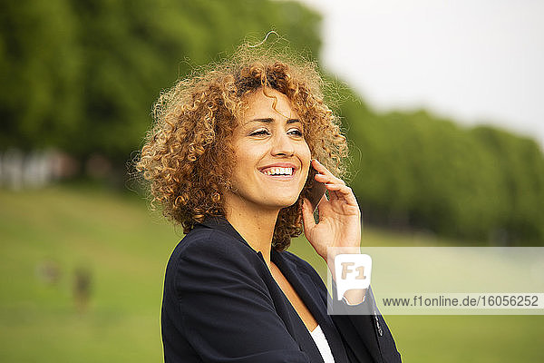 Close-up of smiling businesswoman talking over smart pone while standing outdoors