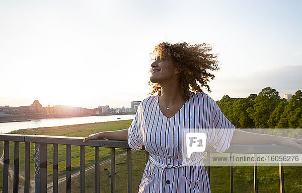 Smiling mid adult woman with curly hair standing by railing against sky at sunset