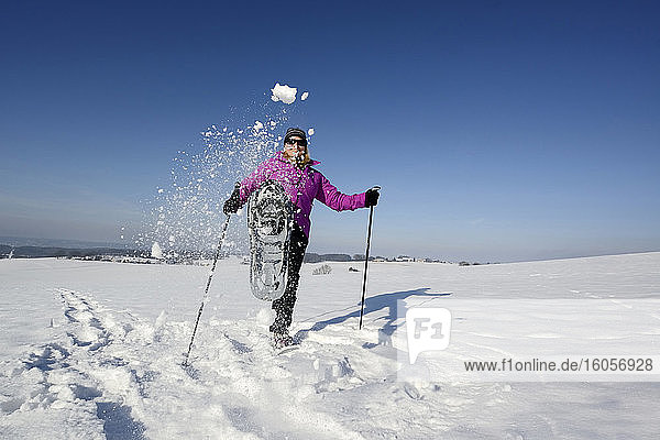 Female hiker kicking snow toward camera