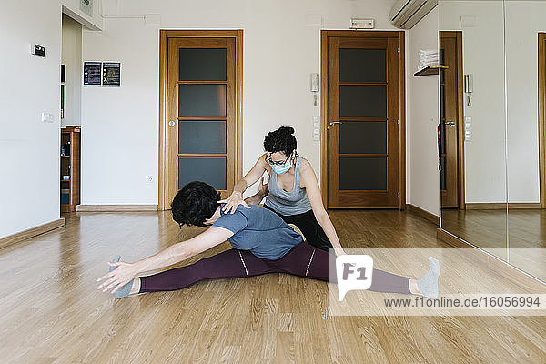 Physiotherapist wearing mask assisting patient in stretching body in health club