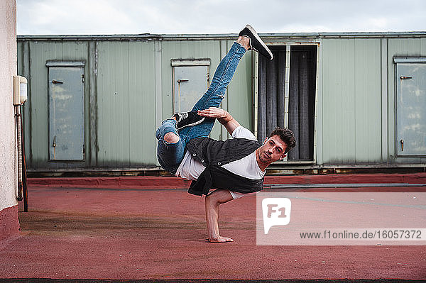 Young man breakdancing on abandoned building terrace