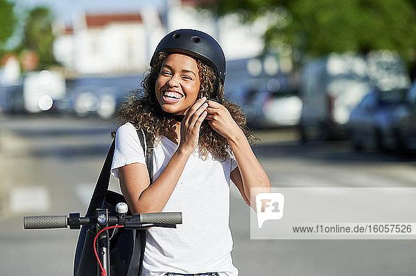 Fröhliche Frau  die einen Helm trägt  während sie an einem sonnigen Tag mit einem Elektroroller steht Fröhliche Frau, die einen Helm trägt, während sie an einem sonnigen Tag mit einem Elektroroller steht