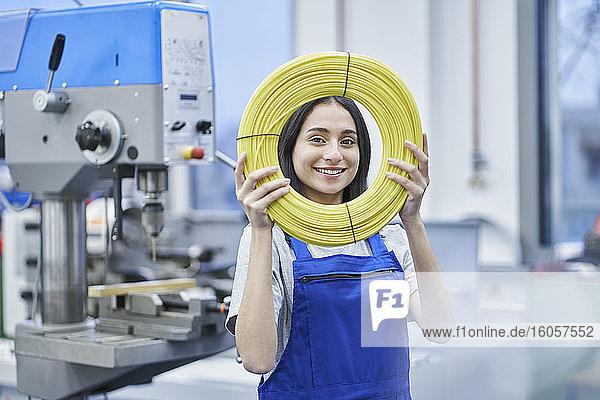Zufriedene Arbeiterin  die in einer Fabrik aufgerollte Kabel durchsieht Zufriedene Arbeiterin, die in einer Fabrik aufgerollte Kabel durchsieht
