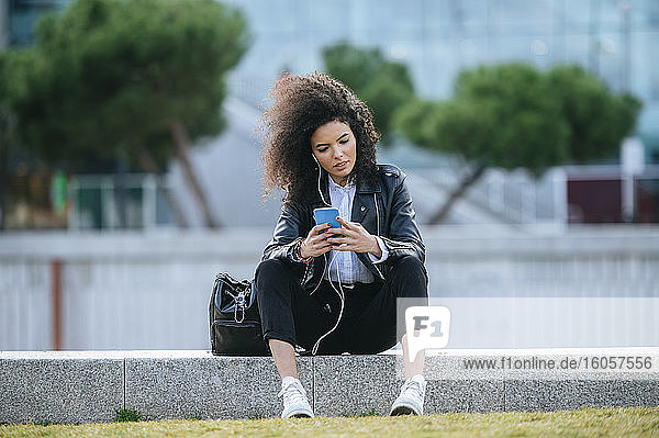 Junge Frau mit Afrofrisur benutzt ihr Smartphone  während sie auf einer Stützmauer sitzt Junge Frau mit Afrofrisur benutzt ihr Smartphone, während sie auf einer Stützmauer sitzt