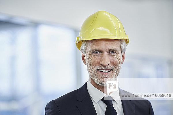 Glücklicher reifer männlicher Manager mit gelbem Schutzhelm in einer Fabrik Glücklicher reifer männlicher Manager mit gelbem Schutzhelm in einer Fabrik