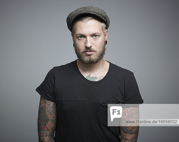 Portrait of young man with tattoos against grey background  close up