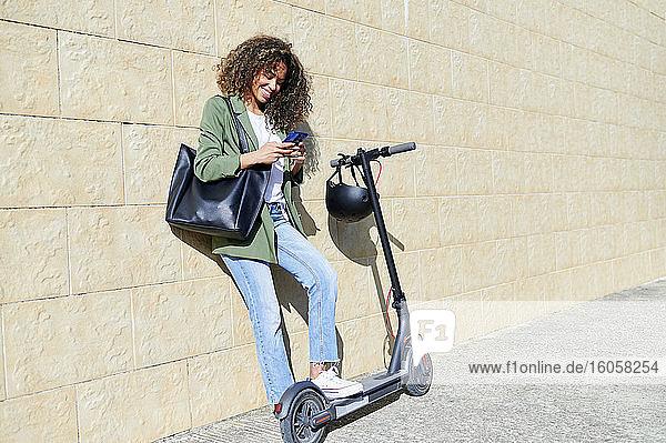 Glückliche Frau  die ihr Smartphone benutzt  während sie mit einem elektrischen Tretroller auf dem Bürgersteig steht Glückliche Frau, die ihr Smartphone benutzt, während sie mit einem elektrischen Tretroller auf dem Bürgersteig steht