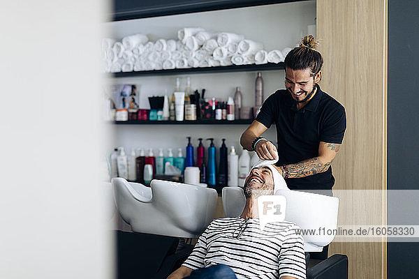 Friseurin wickelt Handtuch auf das Haar eines Kunden im Friseursalon Friseurin wickelt Handtuch auf das Haar eines Kunden im Friseursalon