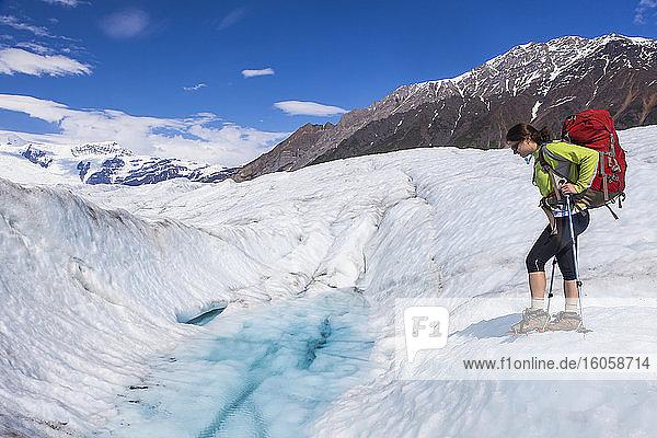 Rucksacktour einer Frau über den Root Glacier mit Steigeisen im Sommer  Wrangell Mountains  Wrangell-St.-Elias-Nationalpark  Süd-Zentral-Alaska; Kennicott  Alaska  Vereinigte Staaten von Amerika