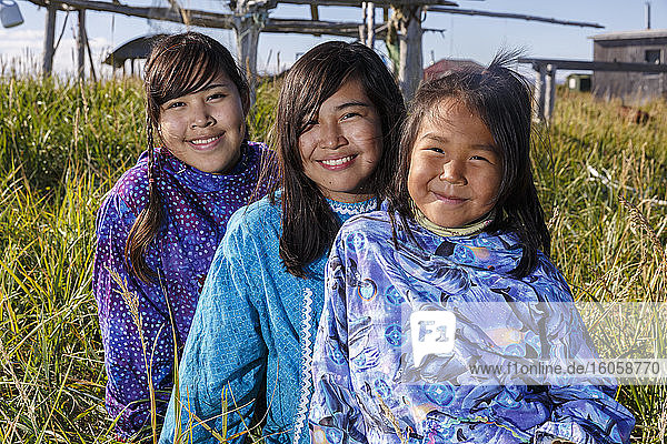 Einheimische Athabaskerinnen aus Alaska in traditionellen Kuspuks  im Gras sitzend mit Fischtrockengestell im Hintergrund Nome  Alaska