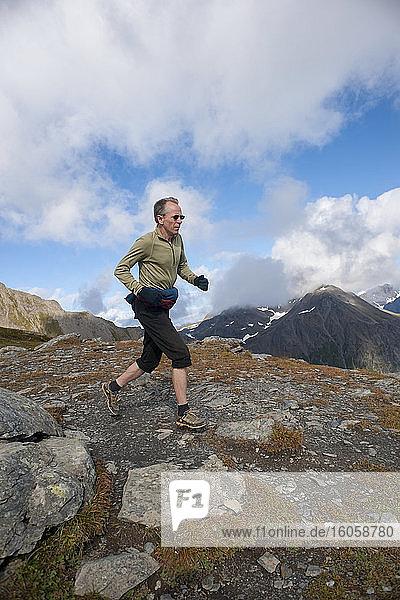 Mann steigt auf dem Gipfelkamm des Mount Marathon Trails aus  oberhalb von Seward  Süd-Zentralalaska  Sommer