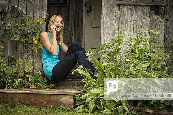 Telefonierende Frau vor einer rustikalen Hütte in Girdwood  Süd-Zentral-Alaska  Sommer