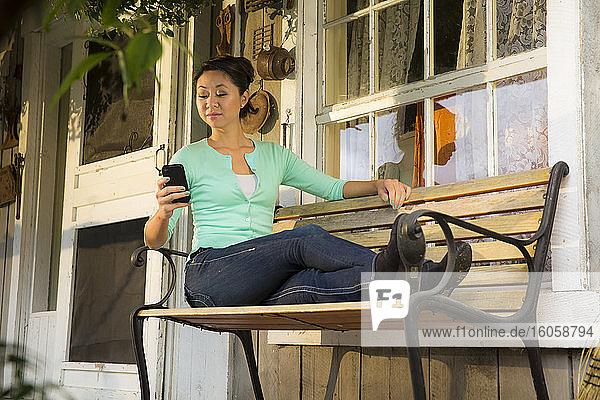 Frau schreibt beim Entspannen auf der Veranda eines rustikalen Hauses in Girdwood  Süd-Zentral-Alaska  Sommer
