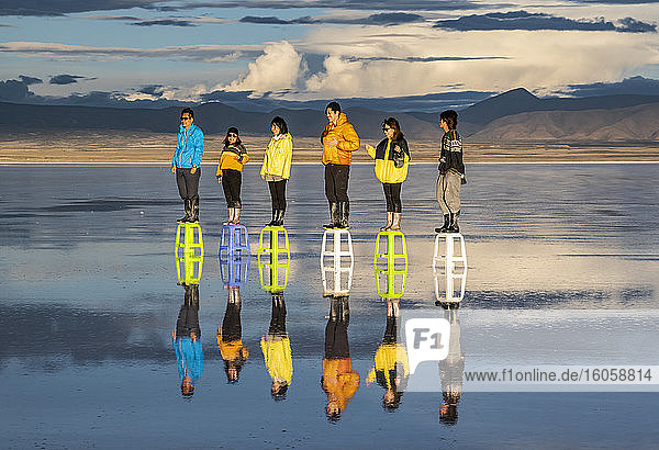Tourists posing in the reflection during the wet season (December-February) in Salar de Uyuni  the world's largest salt flat; Potosi Department  Bolivia