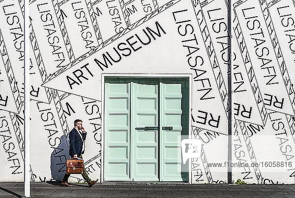 Ein Geschäftsmann geht an Wand und Tür des Kunstmuseums von Reykjavik vorbei; Reykjavik  Island