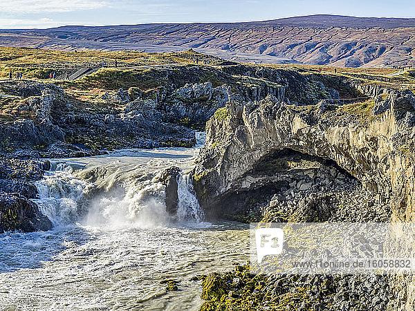 Wasserfall und Fluss  die durch zerklüftetes Gelände fließen  mit Touristen auf einem Pfad zur Besichtigung; Thingeyjarsveit  Nordost-Region  Island