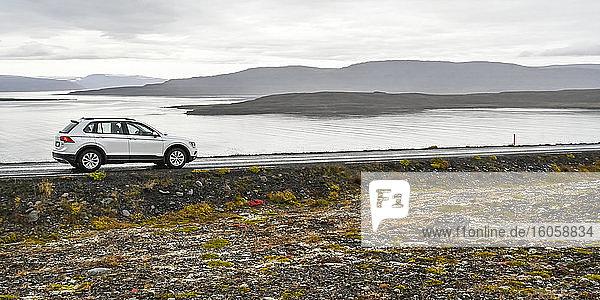 Ein Fahrzeug  das auf einer Straße am Wasser geparkt ist  mit Blick auf den Fjord und silhouettierte Hügel unter bedecktem Himmel; Sudavik  Westfjorde  Island