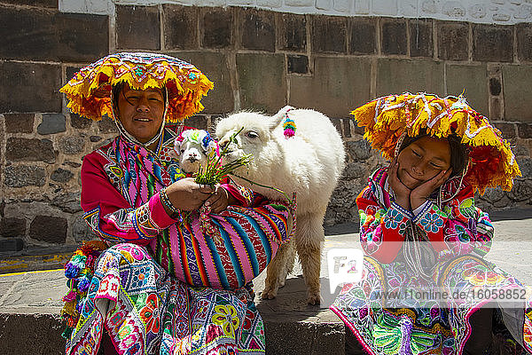 Peruanische Mutter und junge Tochter in farbenfrohen traditionellen Kleidern und Hüten posieren mit zwei Babyalpakas; Cusco  Cusco  Peru
