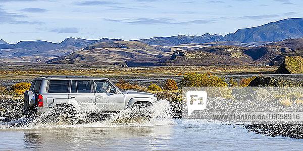 Ein SUV fährt auf einer Schotterstraße durchs Wasser; Rangarthing eyestra  Südliche Region  Island