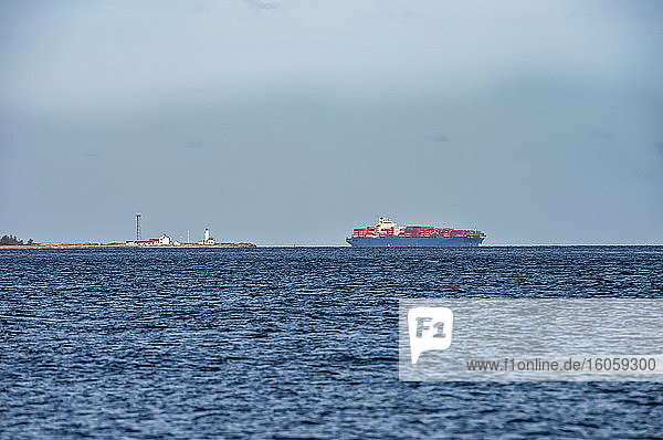 Cargo Ship and lighthouse viewed from Marrowstone Island with blue ocean water and the horizon; Marrowstone Island  Washington  United States of America