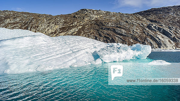 A large iceberg along the coast of Greenland in bright blue water; Sermersooq  Greenland