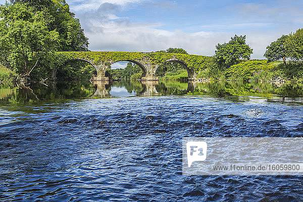 Small rapids on the Blackwater river with an old stone bridge in the background on a sunny day.; Killavullen  County Cork  Ireland