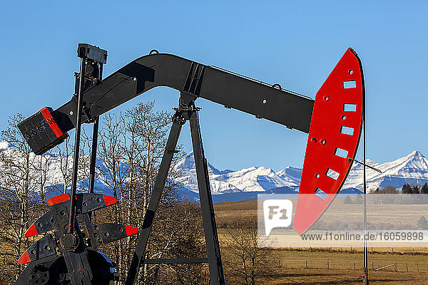 Pumpjack in a field with the foothills and snow-covered Rocky mountains in the background; Alberta  Canada