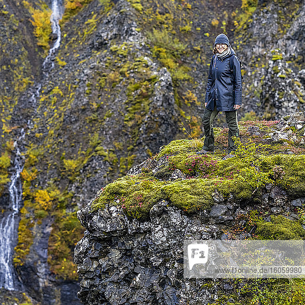 A woman walking at the Glymur hiking trail. Glymur is the second-highest waterfall in Iceland  with a cascade of 198 metres; Hvalfjardarsveit  Capital Region  Iceland