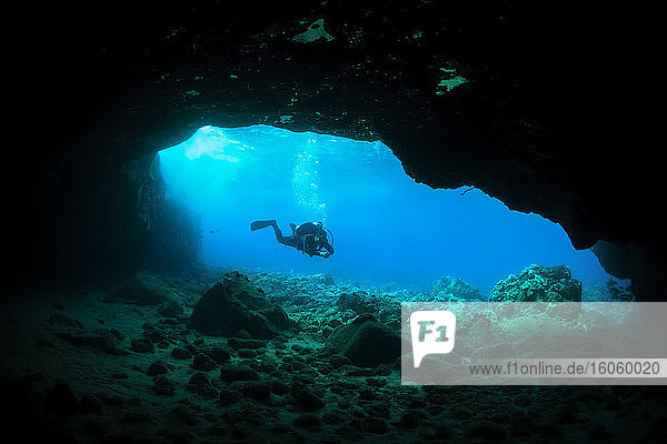 Silhouette of a scuba diver in a cave; Makena  Maui  Hawaii  United States of America