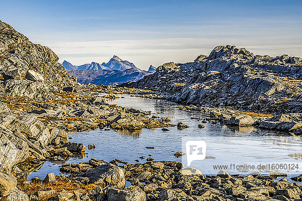 Rocky landscape with water and rugged mountain peaks in the distance; Sermersooq  Greenland