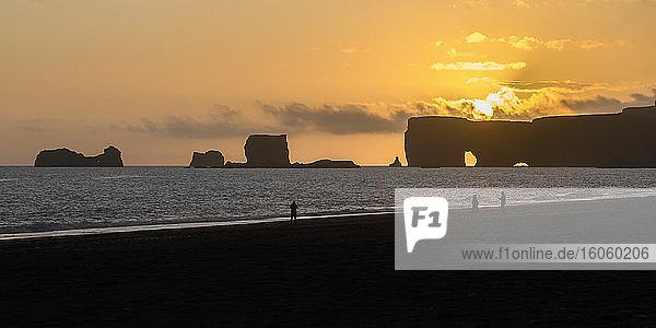Reynisfjara  a black sand beach with rocky sea stacks sillhouetted off the shoreline at dusk; Vik i Myrdal  Myrdalshreppur  Southern Region  Iceland