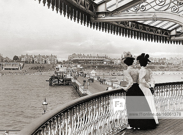 Two women look down on Clacton pier at Clacton-on-Sea  Essex  England towards the end of the 19th century. After a print by an unknown photographer.