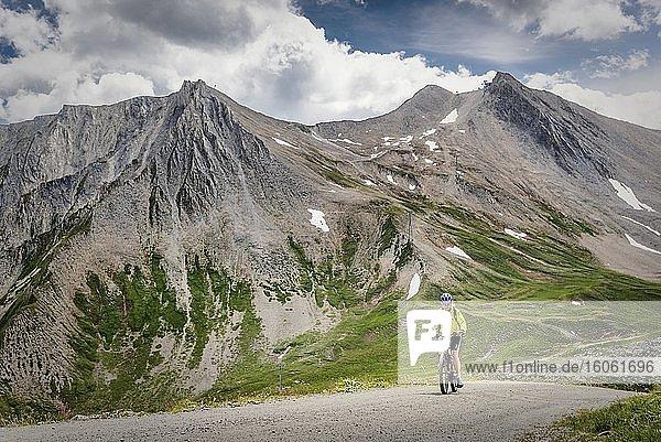 Mountainbikerin fährt auf alpiner Schotterstraße  Serfaus  Tirol  Österreich  Europa