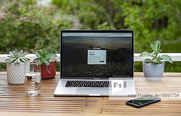 Homeoffice mit Laptop  Apple MacBook Pro mit iPhone X am Schreibtisch  mit geöffnetem Email Programm Microsoft Outlook  Deutschland  Europa
