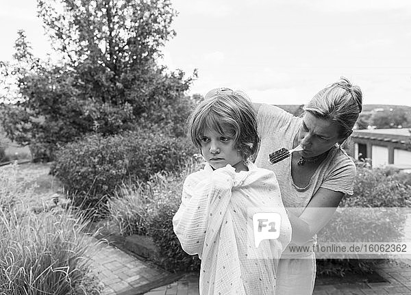 5 year old boy getting his hair cut by mother outside