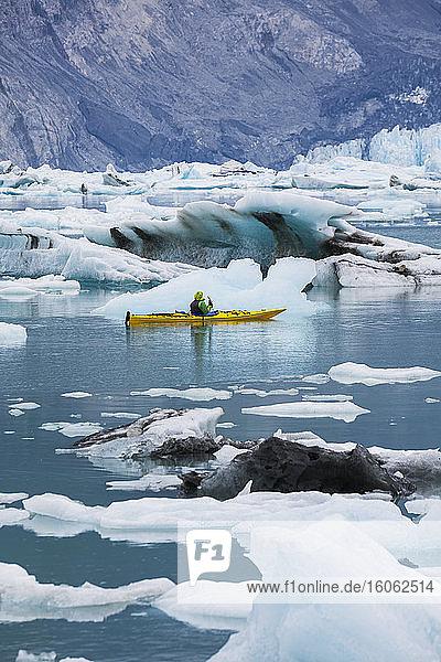 Sea kayaker paddling in glacial lagoon at a glacier terminus on the coast of Alaska