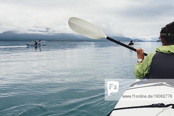 Gruppe von Seekajakfahrern  die in unberührten Gewässern einer Bucht an der Küste Alaskas paddeln. Gruppe von Seekajakfahrern, die in unberührten Gewässern einer Bucht an der Küste Alaskas paddeln.