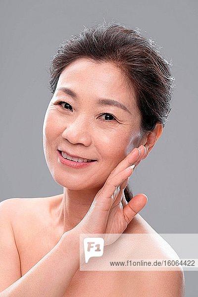 Berühren Sie die Wange mit der Rückseite der Hand eleganten Frauen mittleren Alters