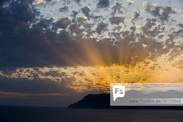 Europe  Italy  Liguria  Ligurian. Spectacular sunset with clouds over Punta Mesco in the Cinque Terre of the Ligurian Sea.