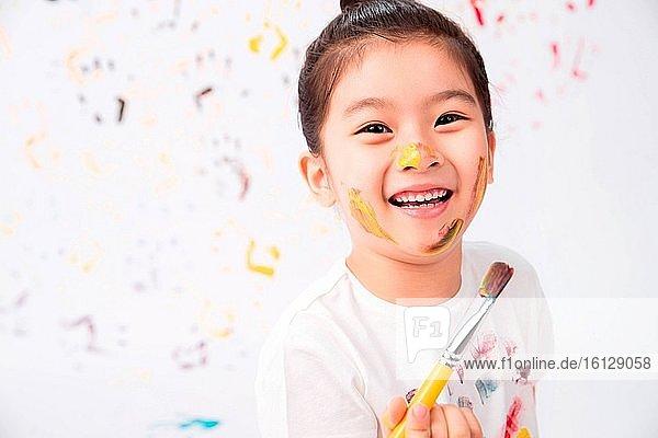 Nimm den Pinsel des kleinen Mädchens zum Malen