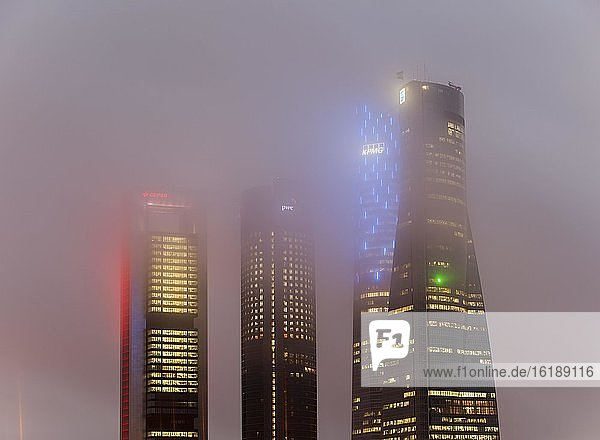 Cuatro Torres Business Area Bürogebäude illuminiert in abendlichen Nebelschwaden  Madrid  Spanien  Europa