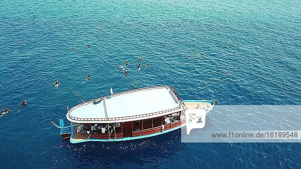 Taucher an Waßeroberfläche neben Tauchboot  Dhoni  Raa Atoll  Malediven  Asien