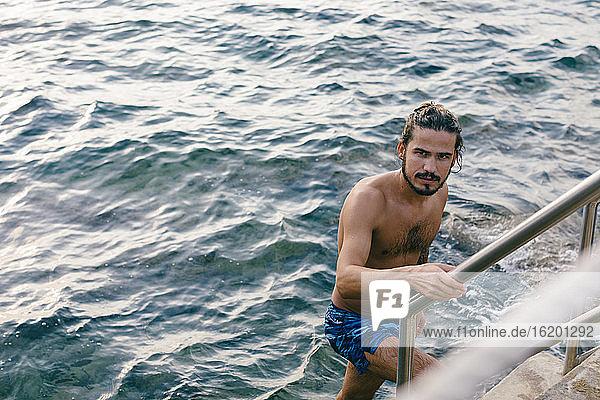 Mann steigt Stufen vom Meer herauf