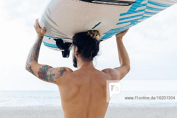 Surfer mit Surfbrett am Meer