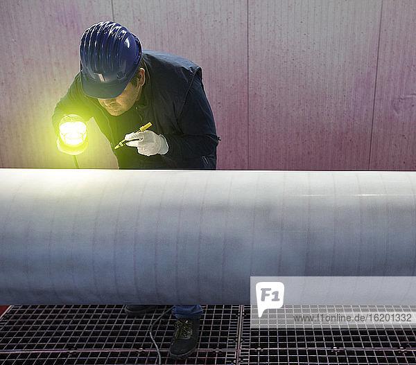 Mann  der in einer Stahlfabrik arbeitet und Stahlrohre inspiziert.
