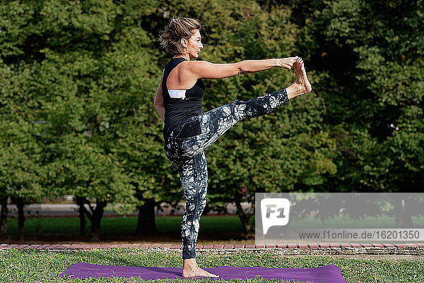 Mature blond woman doing yoga in a park.