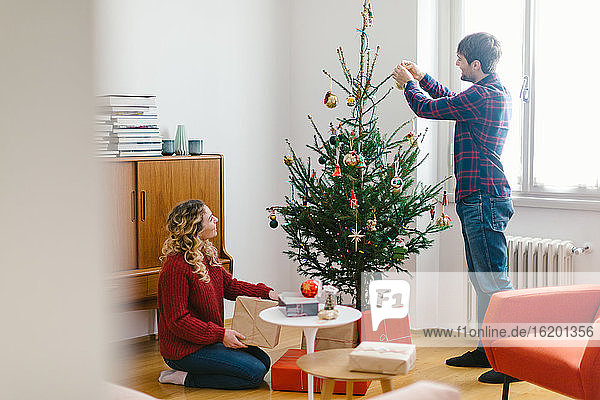 Couple decorating Christmas tree at home