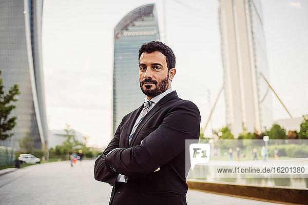 Porträt eines bärtigen Geschäftsmannes in dunklem Anzug  der in die Kamera schaut.