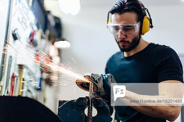 Young man using angle grinder on metal in workshop