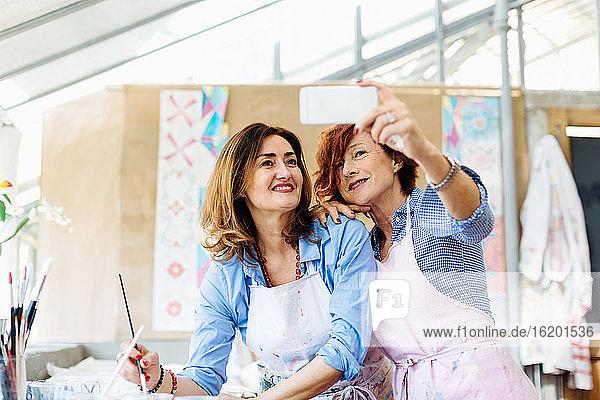 Two women in creative studio  taking selfie  using smartphone